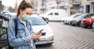 Woman waiting for an Uber on the street wearing a mask.